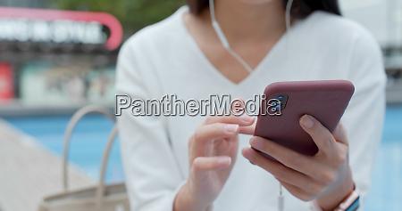 woman listen to music on earphone