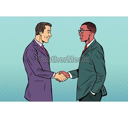 african and caucasian businessmen men handshake