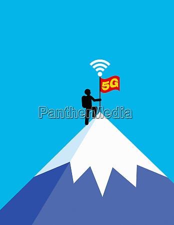 mountaineer placing 5g flag on mountain