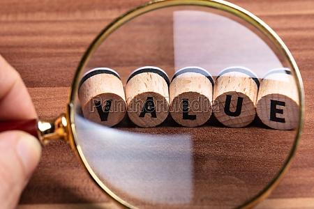 person examining value text through magnifying