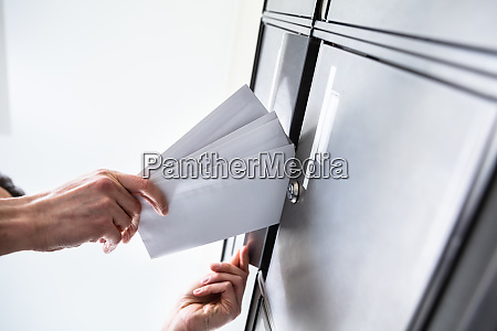 person inserting envelopes in mailbox