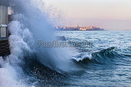 a wave breaks in saint malo