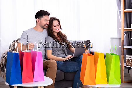 happy young couple shopping on laptop