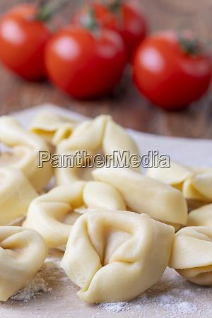 raw tortellini on wood with tomatos