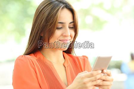 teen in orange uses smart phone