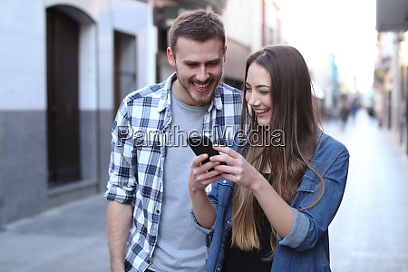 happy couple walking using cell phone