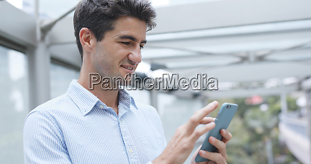 hispanic businessman looking at the cellphone