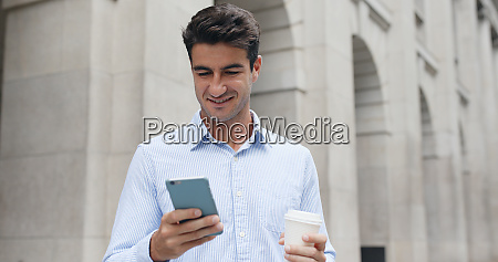 hispanic man looking at cellphone with