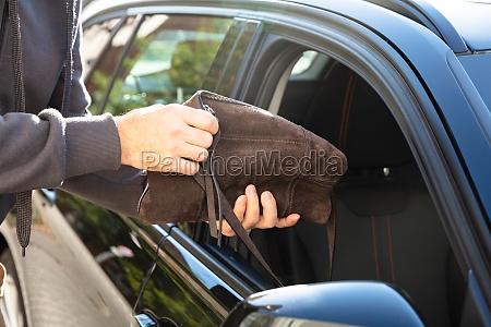 man stealing bag from car