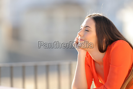 relaxed woman in orange meditating with