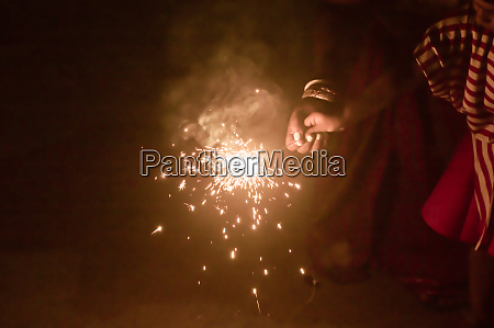 mother and kid holding sparklers on