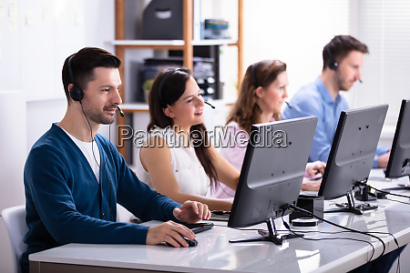 smiling customer service executives using earphones
