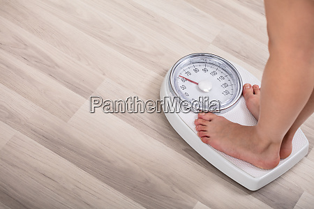 woman standing on weighting scale
