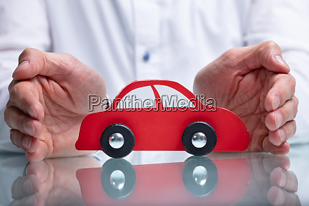 businessmans hand protecting red toy car