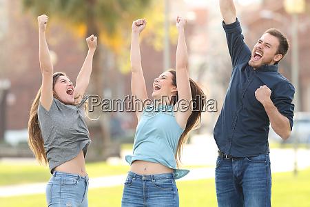 3 joyful friends jumping celebrating success