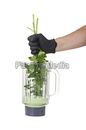 hand holding herbs in a mixer