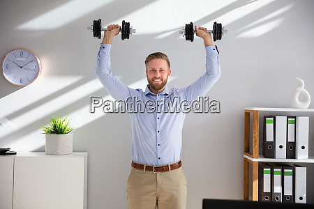 young businessman exercising with dumbbells in