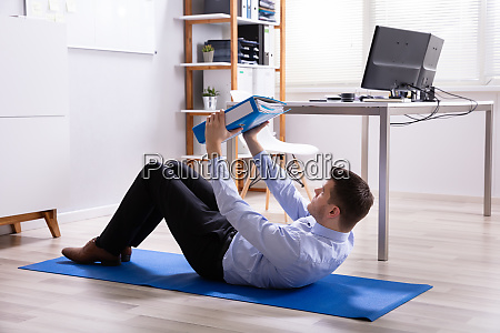businessman doing situps in office