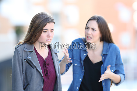 angry woman scolding her guilty friend