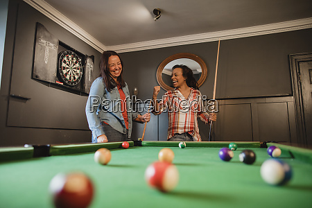 competitive friends playing pool