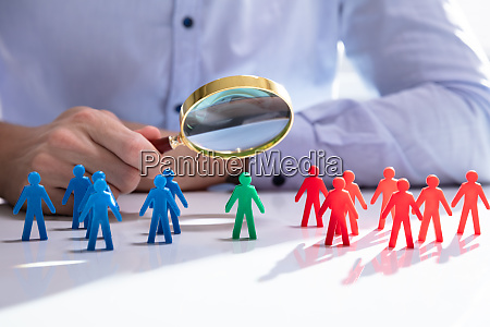 male looking at colorful pawns with