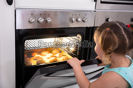 girl baking cookies in oven