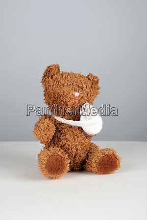 brown teddy bear with a bandaged