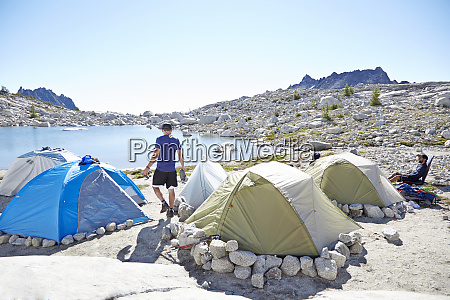 man walking by tents at campsite