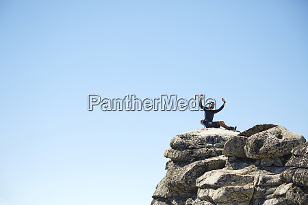 hiker cheering on rocky hilltop under