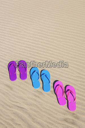 colorful flip flops on sand