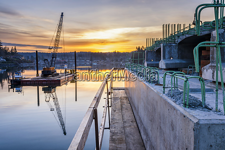 reflection of bridge construction and sunset
