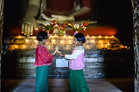 asian girls lighting candles in buddhist