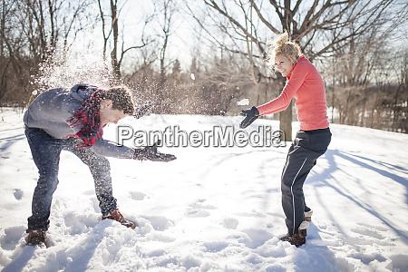 caucasian couple having snowball fight