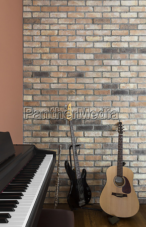 guitars and piano near brick wall