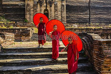 asian monks standing under umbrellas near