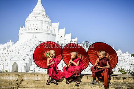 asian monks sitting under umbrellas near