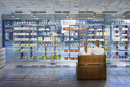 pharmacists sitting in modern pharmacy