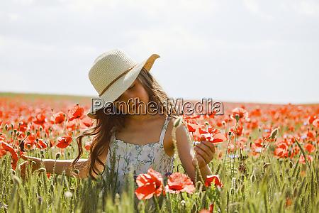 serene girl picking red poppies in