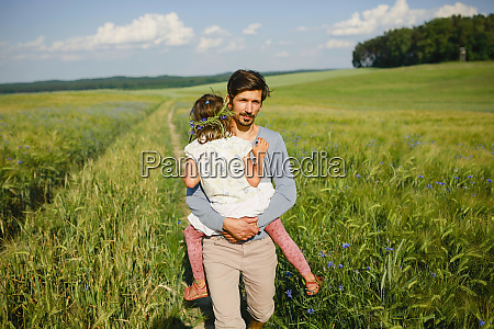 portrait father carrying daughter in sunny
