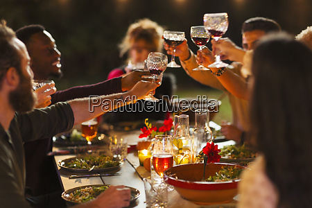 friends toasting wine glasses at dinner