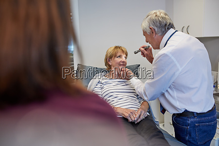 senior doctor examining patient in clinic