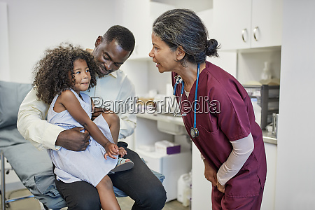 female pediatrician talking to father and