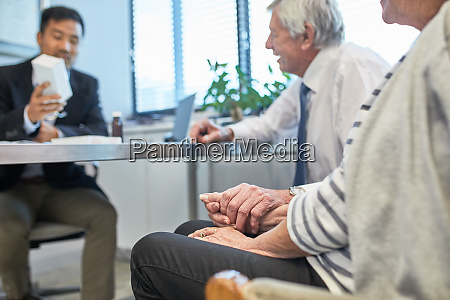 doctor talking with senior couple in