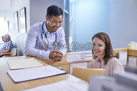 smiling doctor and receptionist discussing medical