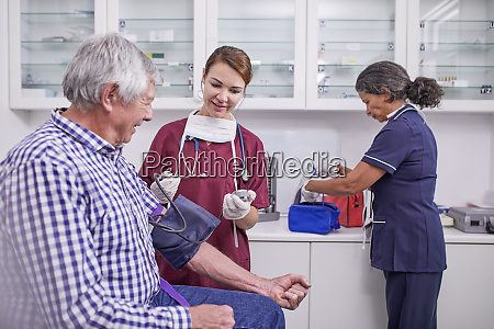 female nurse checking blood pressure of