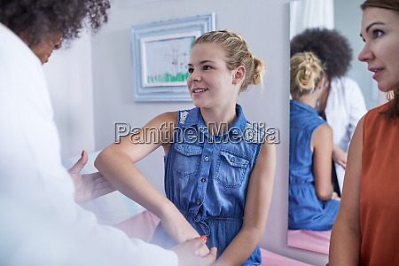 female pediatrician examining arm of girl