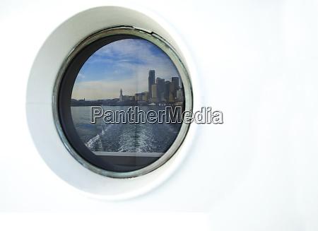 city skyline reflected in ferry porthole