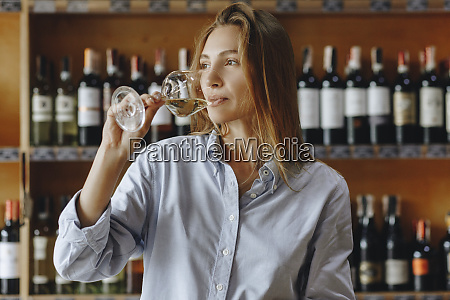 young woman drinking glass of white