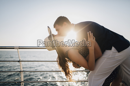 man dipping and kissing woman on