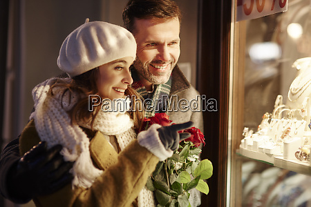 smiling couple looking in shop window